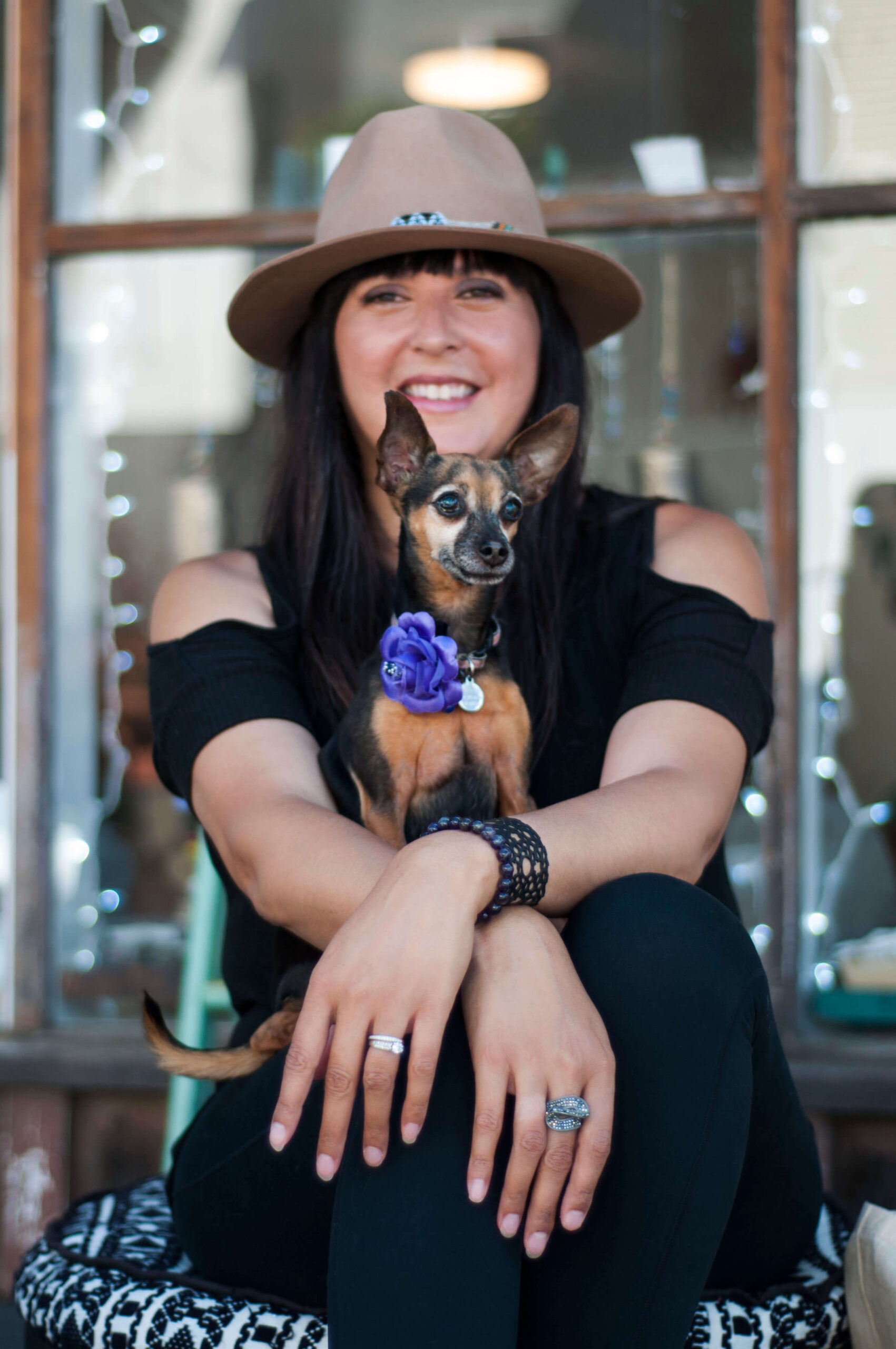 Denise Clifton dressed in black, sitting cross legged with a chihuahua on her lap